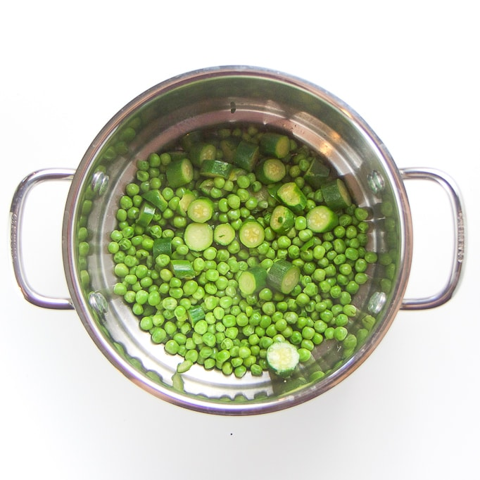 Silver steamer basket filled with steamed peas and zucchini.