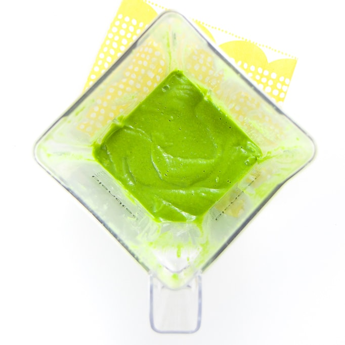 A clear blender filled with a smooth green baby food puree.