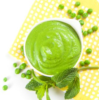 White bowl filled with green pean and mint baby food puree.