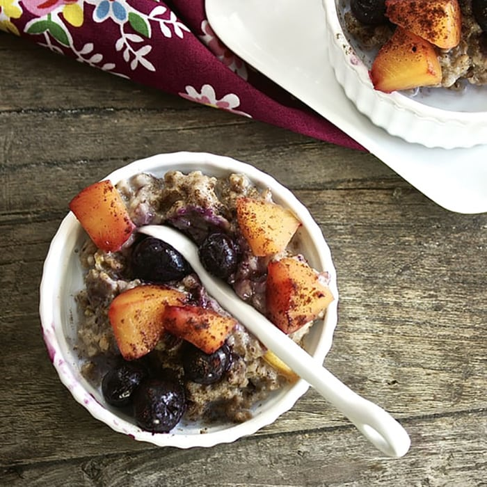small bowl with oatmeal, peaches and blueberries inside for toddler.