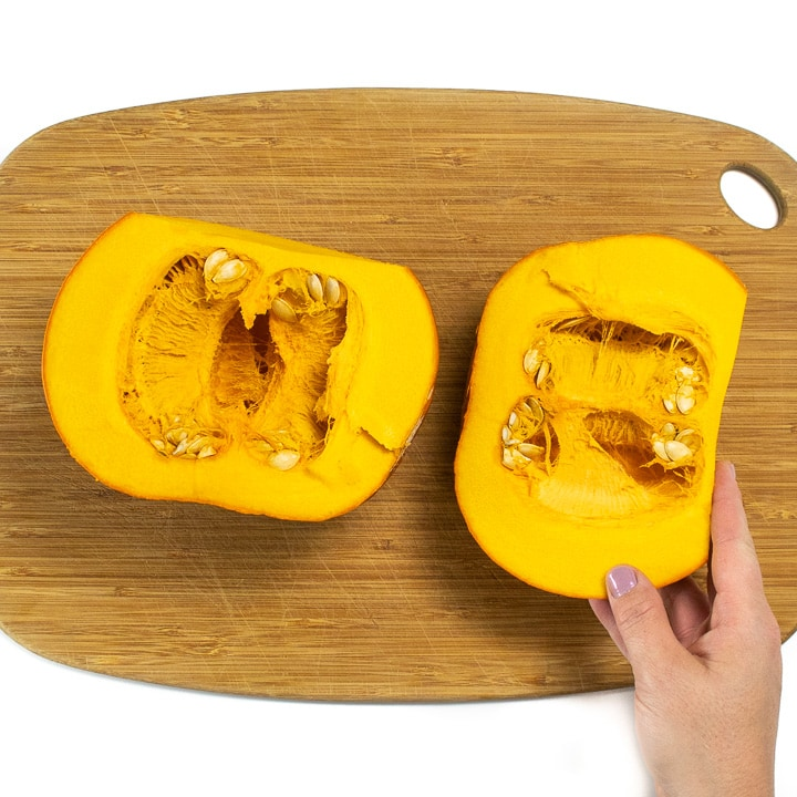 Pumpkin on a cutting board chopped in half.
