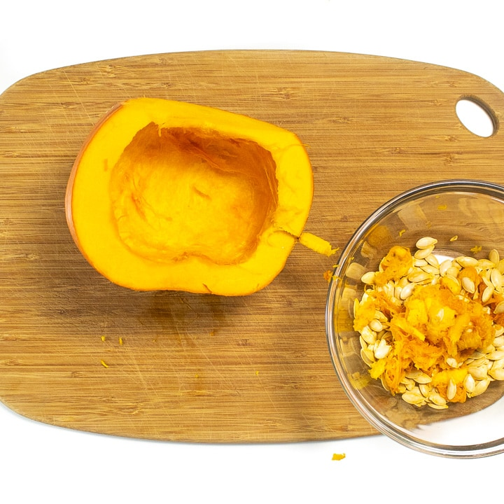 Pumpkin on a cutting board with seeds out and in a bowl.