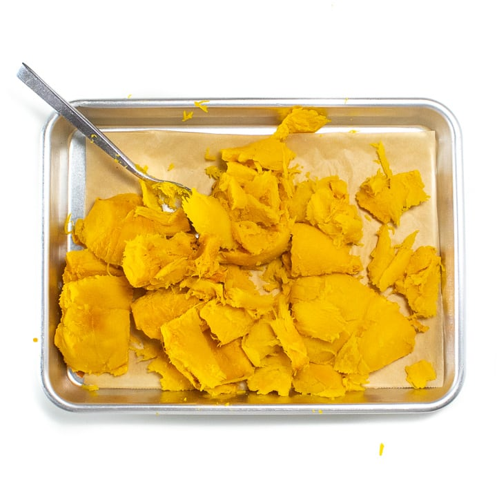 A baking sheet with chunks of roasted pumpkin without the skin.