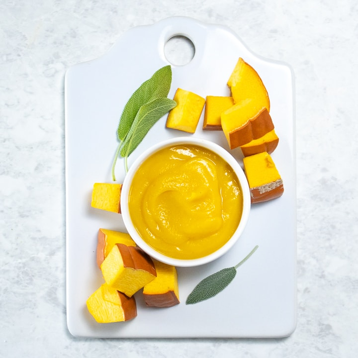 spread of a bowl of pumpkin puree for baby on a white board with chunks of pumpkin and sage around it.