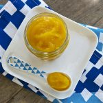 white square plate with glass jar filled with pumpkin baby food puree with a spoon nestled next to it filled with puree.