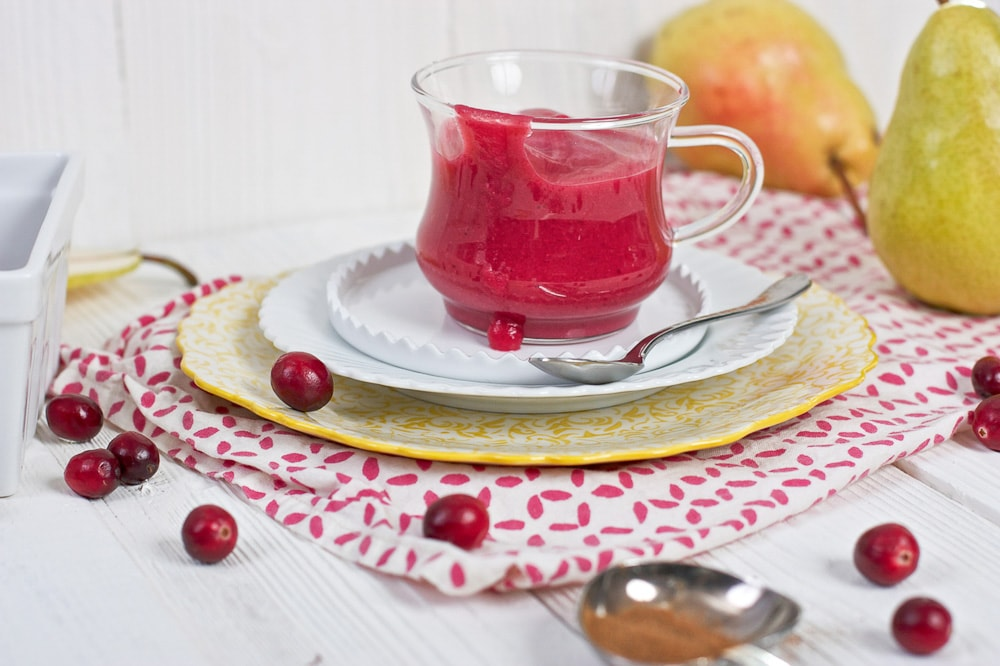 Clear jar filled with a cranberry baby puree sitting on a stack of plate.