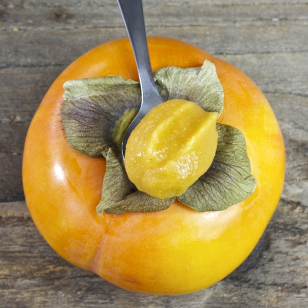 A silver spoon with baby food puree sitting on top of a persimmon.