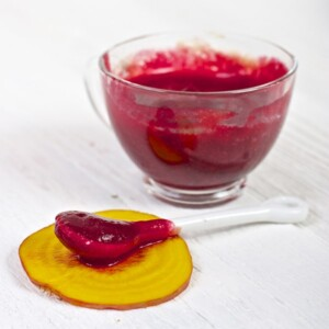 clear jar filled with red beet puree with a spoon sitting in front of it resting on a piece of golden beet.