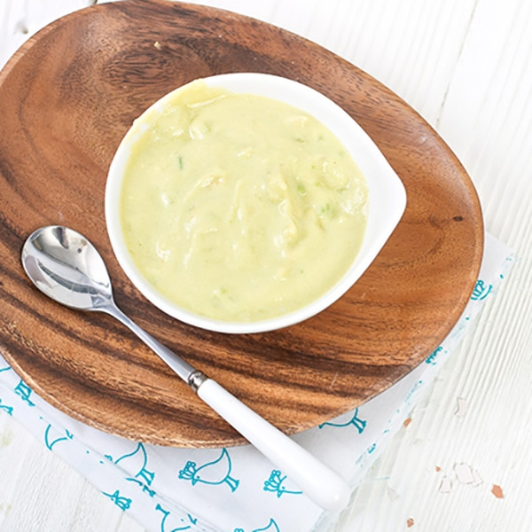 white bowl sitting on an oval wooden plate with a silver and white spoon resting on top. The small white bowl is filled with an egg and avocado baby food puree.