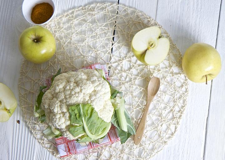 Cauliflower on a white board with napkin underneath it.