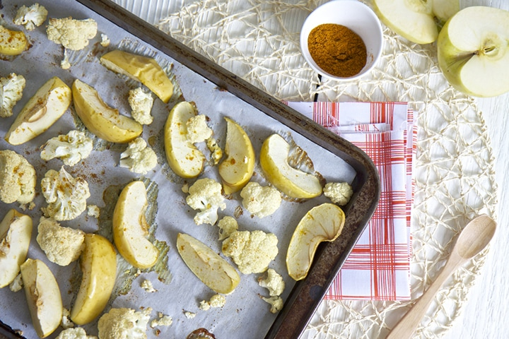 Baking sheet with produce scattered on top.