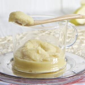 Glass bowl filled with homemade puree with spoon resting on top.