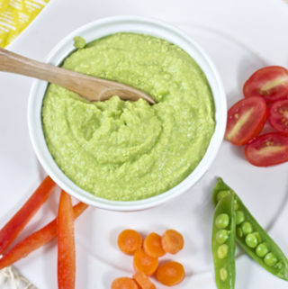 Image is of a small bowl filled with hummus on a plate with chopped veggies.
