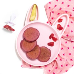 Pink bunny plate for baby or toddler filled with pink pancakes, raspberries and avocado sitting on a pink napkin with a white fork for baby to use.