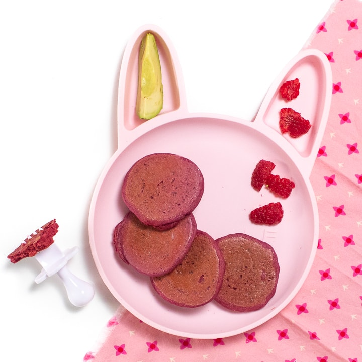 Pink bunny plate for baby or toddler filled with pink pancakes, raspberries and avocado sitting on a pink napkin.