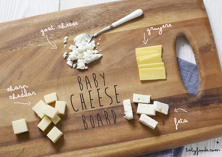 Cutting board with a selection of cheeses for baby on it.