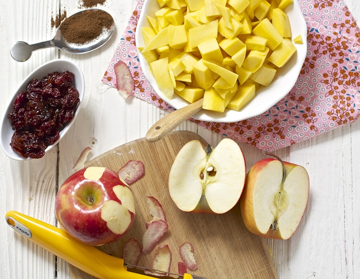 Mango, apples and cherries spread out on a white board.