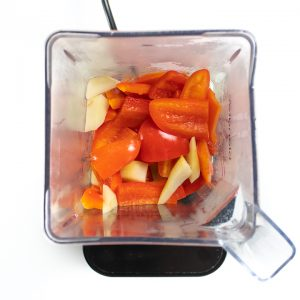 Blender with cooked red pepper and pear.