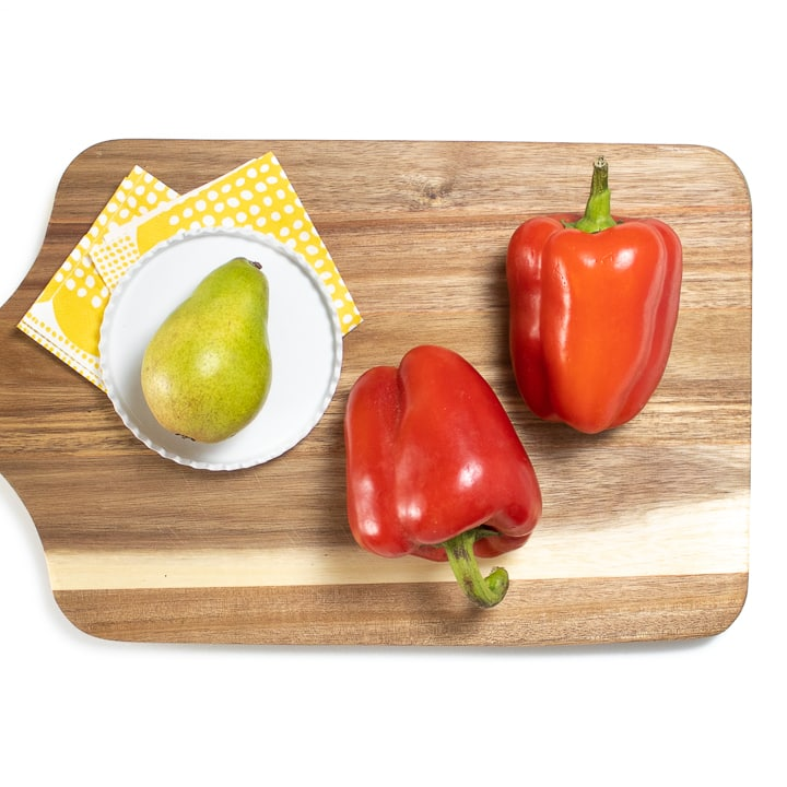 Red pepper and pear on a cutting board.