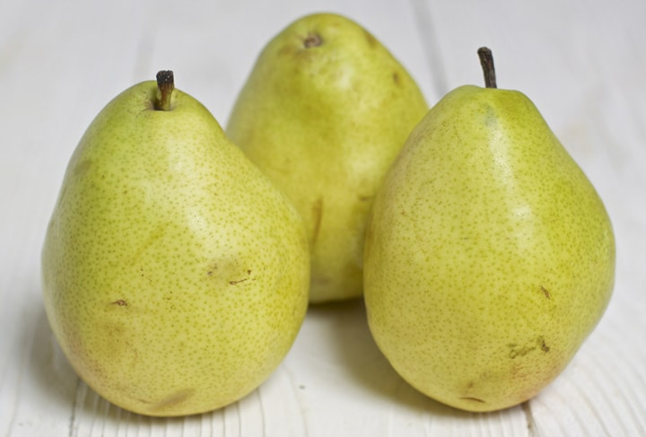 3 pears standing on a white board.