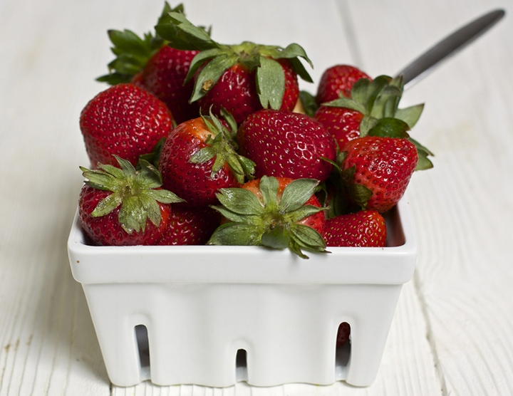 White fruit basket with fresh strawberries inside.