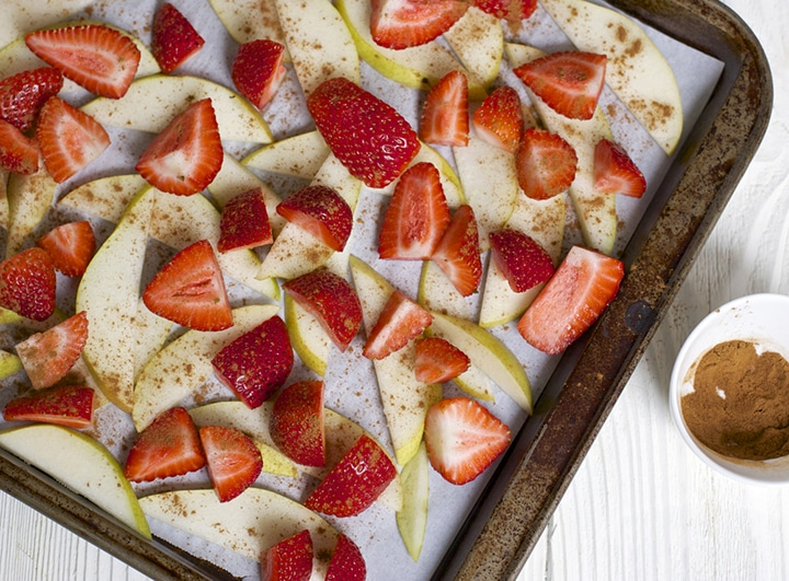Strawberries and pears on a baking sheet.
