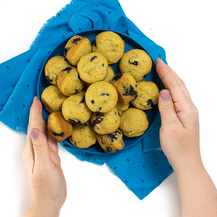 Hands holding a blue kids plate pilled high with blueberry muffins.