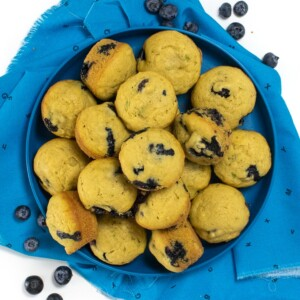 Blue kids plate with blueberry muffins pilled high and blueberries scattered around.