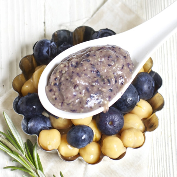 Spoon filled with baby food puree rising on a dish filled with blueberries and chickpeas.