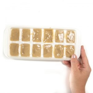 A hand holding a freezer tray full of a banana puree for baby.