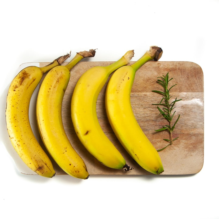 bananas lined up on a cutting board with rosemary ready to make into a homemade baby food meal.