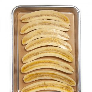 bananas lined up on a baking sheet ready to get roasted for a baby food puree.