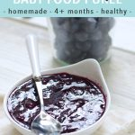 graphic for post - text reads - blueberry baby food puree - homemade - 4+ months - healthy. Image is of small white bowl filled with a blueberry baby food puree inside. bowl has a white and silver spoon resting on top and is sitting on a white surface.