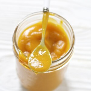 Glass jar filled with a thick homemade baby food puree with a spoon resting on top.