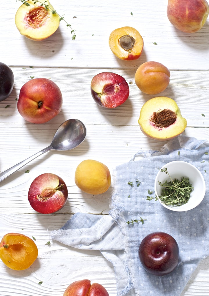 stone fruit and thyme scattered on top of white wooden board.
