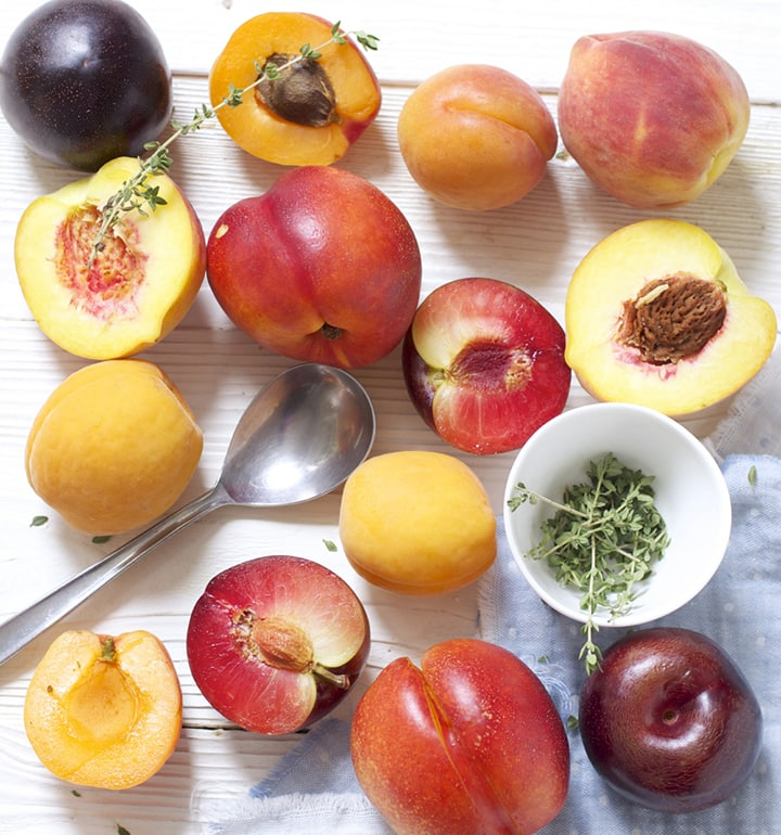 Scatter of stone fruit and thyme on a white wooden board.