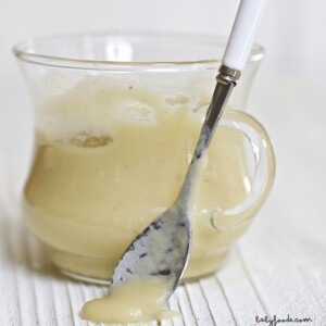 Image is of a clear jar filled with a smooth apple baby food puree with a silver and white spoon resting against the jar with puree dripping off of it.