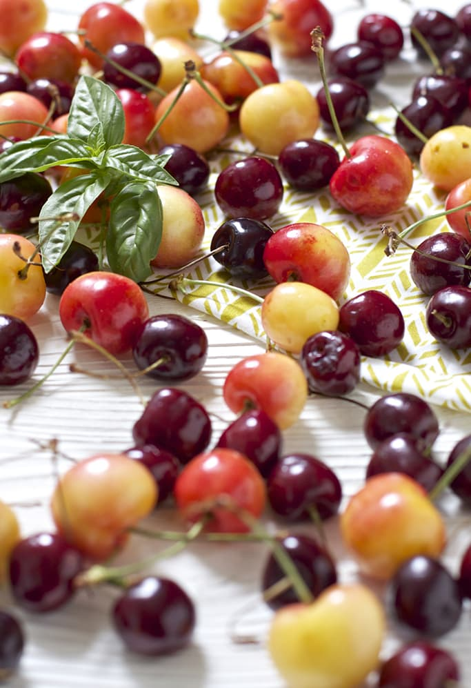 A bunch of sweet and tart cherries scattered across a white wooden board with a basil leaf in the middle.