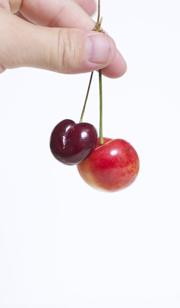 Side shot of fingers holding on to 2 cherries by the stems.