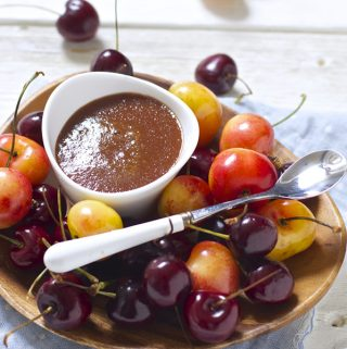 small white bowl sitting on a wooden plate that is filled with whole cherries. In the bowl is a thick red cherry baby food puree.