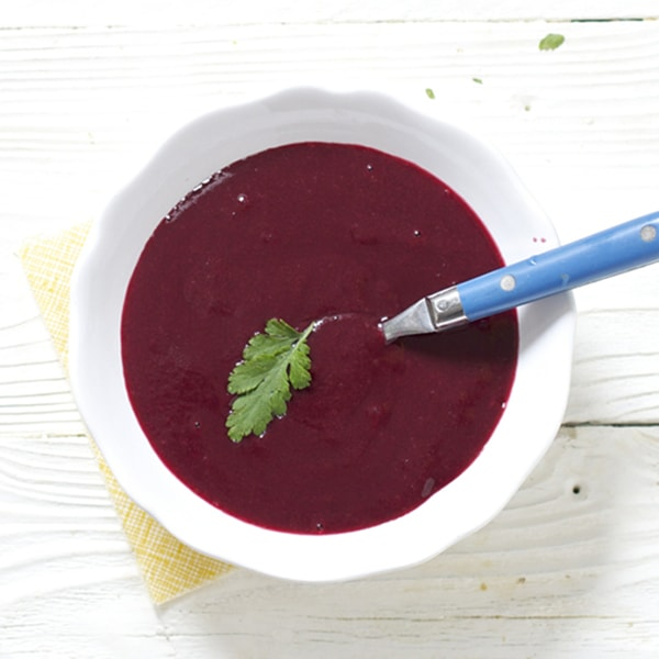 Small white bowl filled with bright purple baby food puree.