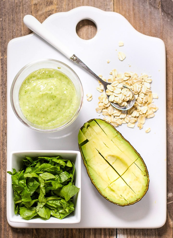 Image is of a white cutting board with a spread of produce and a small bowl filled with a healthy homemade puree.