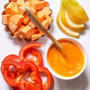 White cutting board with a spread of produce on it with a bowl of smooth baby food.