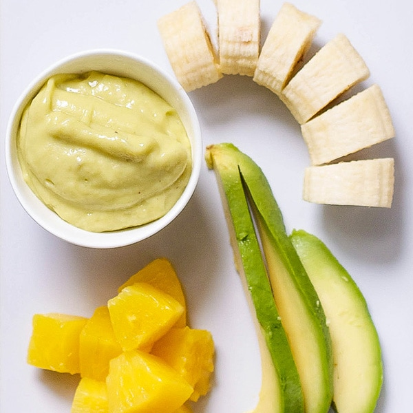 Image is of a white cutting board with a spread of produce and a small bowl filled with a creamy homemade baby food puree.
