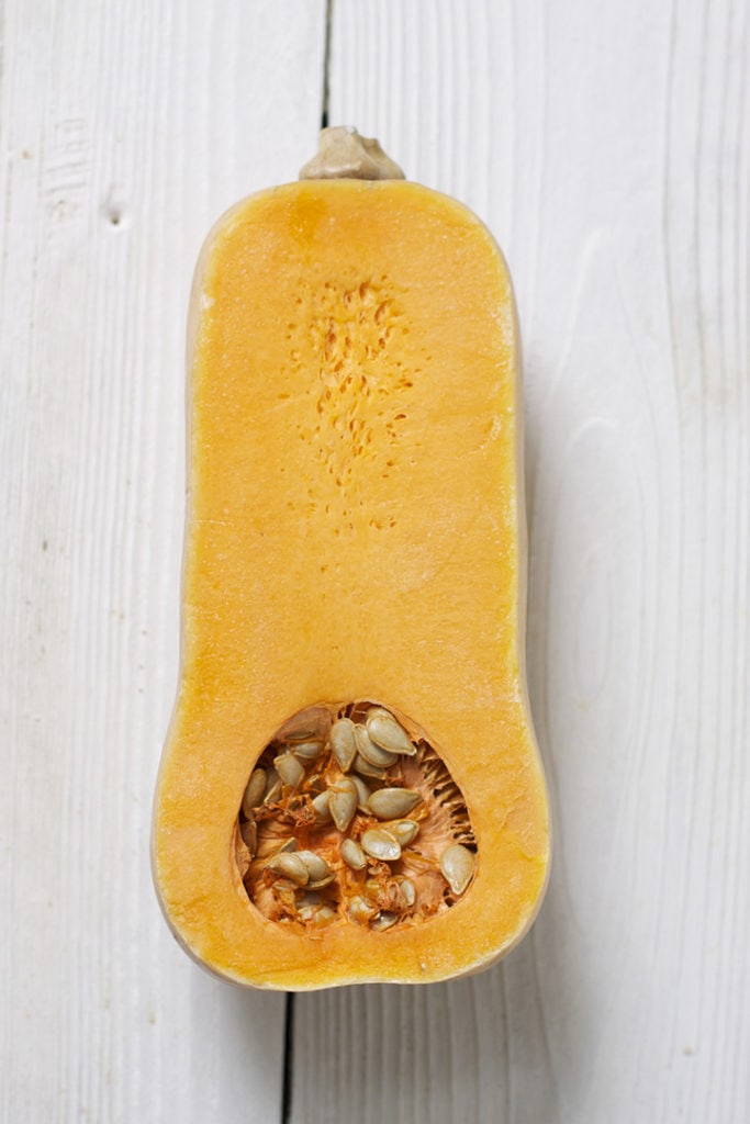 Butternut squash cut in half on a white board.