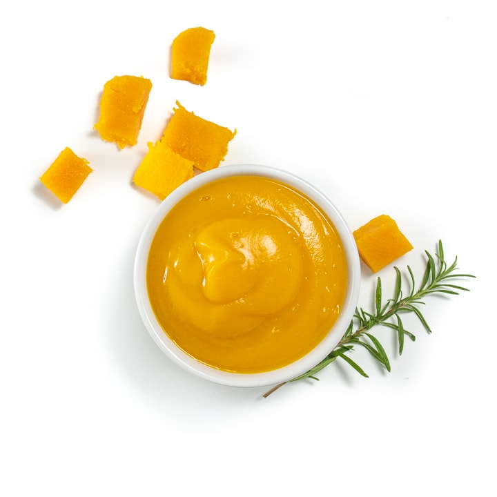Spread of a small bowl of butternut squash puree along with chunks of butternut squash, rosemary and a white baby spoon.