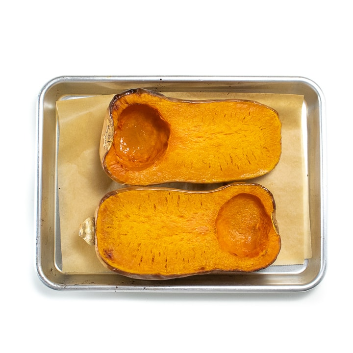 Roasted butternut squash laying on a baking sheet.