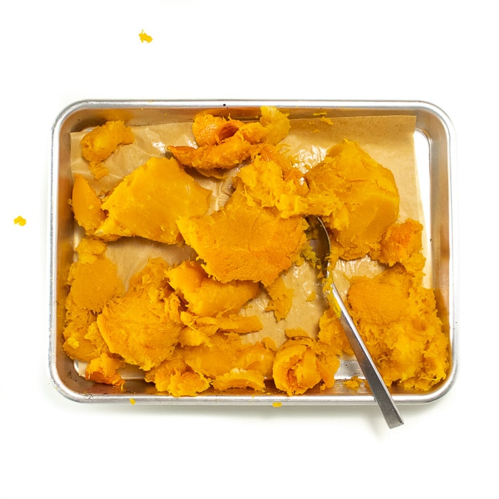Chunks of roasted butternut squash with the skin off on a baking sheet.