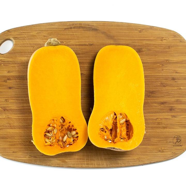 A butternut squash cut in half sitting on a cutting board.