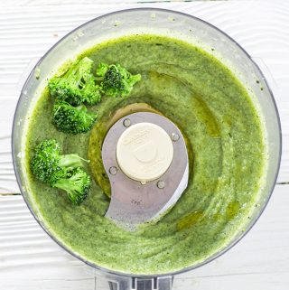 food processor is filled with a thick green broccoli puree with a few chunks of broccoli on the side.